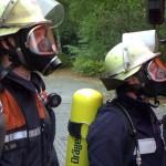 Atemschutzgeräteträger vor einer Übung - einmal im Nomex-Schutzanzug, einmal im sog. Bonner Anzug. Im Realeinsatz wird nur der Nomex-Schutzanzug mit angelegter Flammschutzhaube (im Kragen)getragen.