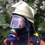 PA-Träger mit angelegter Dräger Panorama-Nova-Maske mit Einheitssteckanschluß (erkennbar an der roten Abdeckkappe) und angelegter Flammschutzhaube