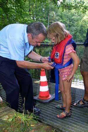 Sicher ist sicher – ein Feuerwehrmann legt einer kleinen Besucherin eine Schwimmweste an. Dann geht es ins Schlauchboot auf den Hofteich. Foto: Florian Büh