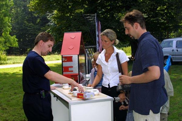Brandmelder bringen Sicherheit ins Haus. Ein Feuerwehrmann berät Besucher beim Kinder- und Sommerfest. Foto: Florian Büh