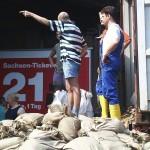 Mit Containern (Bildrand rechts) werden ständig mehr Sandsäcke herangefahren
