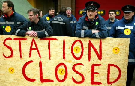 Firefighters walk out at the start of their eight-day strike at Cowcaddens fire station in Glasgow, November 22, 2002. Angry British firefighters pressed ahead with the strike on November 22 after all-night talks over pay failed to clinch a deal. REUTERS/Jeff J Mitchell