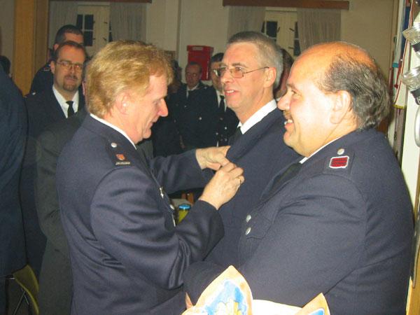 Werner Sannmann (Direktionsbereichsführer Ost-Süd) steckt Jens Albers die Auszeichnung an. Rechts im Bild: Bernd Johannsen