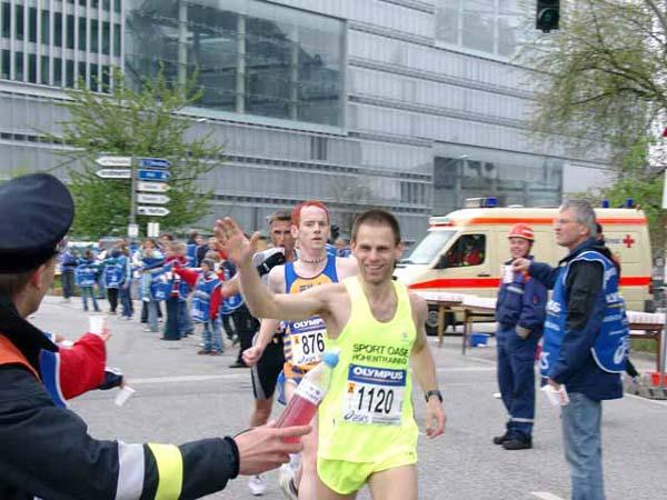 Übergabe des Elektrolytgetränkes an den Läufer