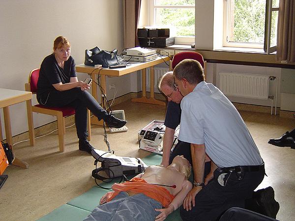 Frau Dr. Möser im Gespräch mit den Hauptbrandmeistern Frank und Ingo Meyer während des Defibrillationstrainings
