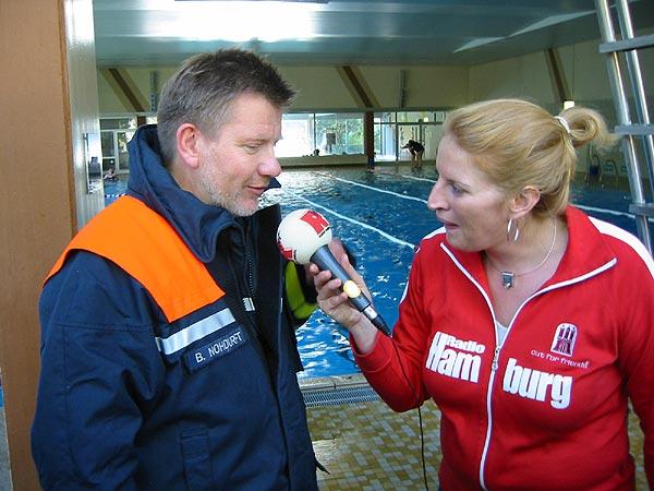 Radio Hamburg Moderatorin Birgit Hahn fragt Wehrführer Bernd Nohdurft, wer ihn angemeldet haben könnte.