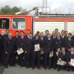 Die Gruppe der 17 Prüflinge nach bestandener Prüfung mit einigen ihrer Ausbilder (Hintergrund: TLF 16/25 der FF Rissen)