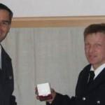 Rainer Kohrs bekommt von Michael Bauer den Orden überreicht.
