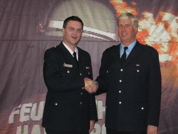 Gerhard Mögling (rechts) nimmt die Glückwünsche vom Bereichsführer Eimsbüttel und stellvertretenden Direktionsbereichsführer West Jörg Schultze-Scheer entgegen