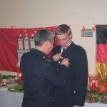 Wehrführer Thomsen Stern bringt an Reinhards Uniform das Abzeichen für 25 Jahre FF-Zugehörigkeit an.