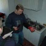 Verletztensitutation in der Küche: eine Person hat sich beim Brotschneiden in den linken Unterarm geschnitten.