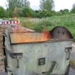 Ein mit Holz gefüllter Müllcontainer brennt lichterloh, aber die Feuerwehr ist gleich da.