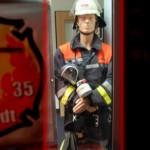 Stimmt. Wie ein Feuerwehrmann. Nur ist dies ein Modell eines Feuerwehrkameraden. Aber warum steht dieses Modell in einer Haspa-Filliale?