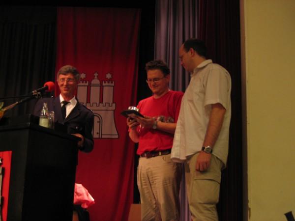 Der Landesbereichsführer Hermann Jonas überreicht den Vertretern der Kommunity GmbH, v.l. Markus Leder und Tom Müller-Kortkamp, eine Ehrenurkunde sowie ein kleines Präsent zur Anerkennung der Leistung