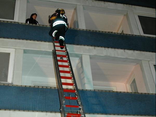Der 1. Angriffstrupp geht zur Menschenrettung über die Schiebeleiter zum 3. Obergeschoss vor
