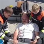 Andre Voß und Malte Kantak versorgen eine Person mit Brandverletzungen an beiden Unterarmen.