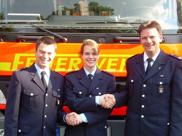 Der Wehrführer David Märtig (rechts im Bild1) und Jugendfeuerwehrwart Oliver Mücke (links im Bild1) gratulieren Julia Oester-Barkey.
