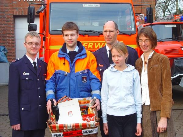 JFW Matthias Hedemann und Marcel Riese überreichen dem Jubilar einen Präsentkorb. Tochter Lara und Ehefrau Marion freuen sich mit ihm. (v. links)