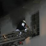 Ein Feuerwehrmann versucht sich einen Zugang über das Fenster zu verschaffen.