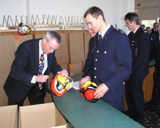 Foto: D.Frommer / Jürgen Kalweit von HFUK Nord (links) übergibt Helme an Björn Wendt