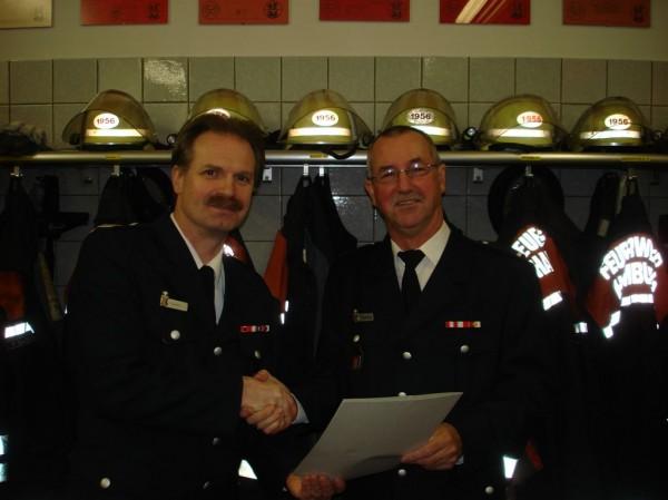 Wehrführer Holger Larsen überreicht die Urkunde für den Übertritt in die Ehrenabteilung.