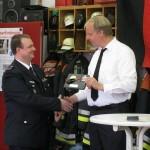 Wehrführer Fabian Keller überreicht eines der Geschenke der Wehr nach seiner Ansprache.