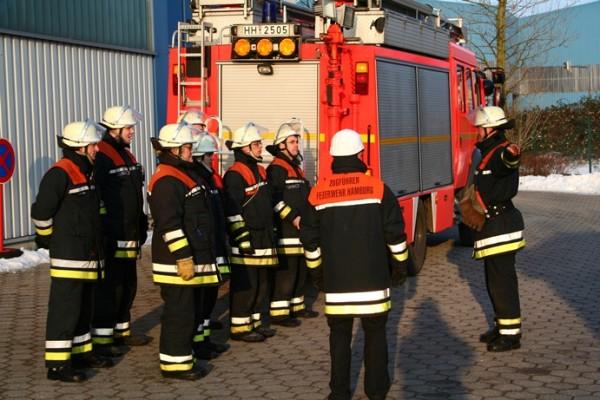 Die Gruppe tritt hinter dem Fahrzeug zum Brandschutzeinsatz an.