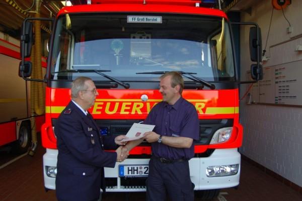 Bereichsführer Uli Wechsung übergibt dem neuen Wehrführer Andreas Meyer seine Urkunde.
