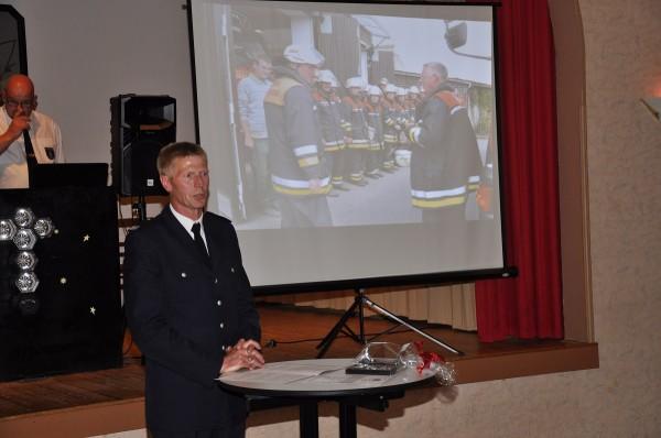 Wehrführer Heiner Meyns ehrt den Jubilar stellvertretend für die gesamte Wehr. Im Hintergrund einige Bilder seiner letzten Übung