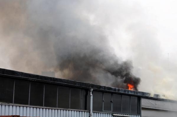 Flammen und Rauch aus dem Dach der Lagerhalle
