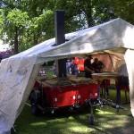 Die neue Feldküche in einsatzbereitem Zustand, aus Wetterschutzgründen im Zelt. Die seitlichen Behälter werden abgenommen und als Ausschanktresen verwendet.