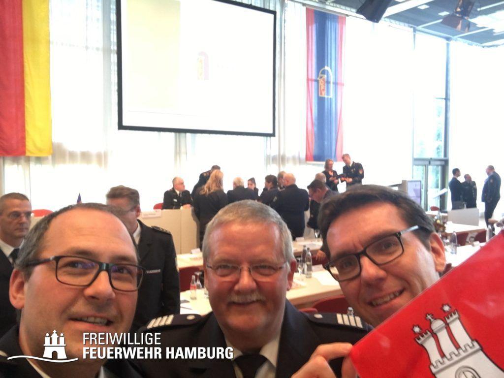 Gruppenselfie: Harald Burghart, Andreas Neven und Kai Winter (von links) vertreten die Freiwillige Feuerwehr Hamburg mit hochgehaltener Flagge.